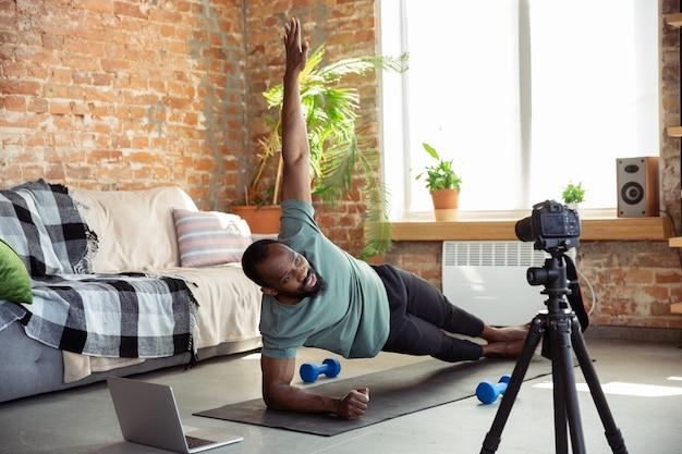 Jovem afro-americano, ensinando em casa cursos on-line de fitness, estilo de vida aeróbico e esportivo durante a quarentena, gravação na câmera, streaming