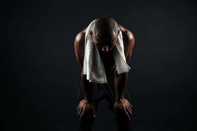 Jovem afro americano esportes homem de pé com uma toalha branca, descansando depois de treino