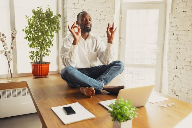 Jovem afro-americano fazendo ioga em casa enquanto está em quarentena e trabalhando online freelance