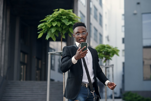 Jovem afro-americano feliz caminhando pela cidade ensolarada