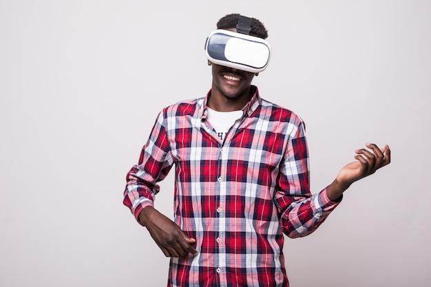 Jovem afro-americano, feliz e animado, usando óculos de visão de realidade virtual vr 360 e jogando videogame