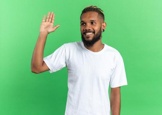 Jovem afro-americano feliz em uma camiseta branca olhando para o lado sorrindo alegremente acenando com a mão