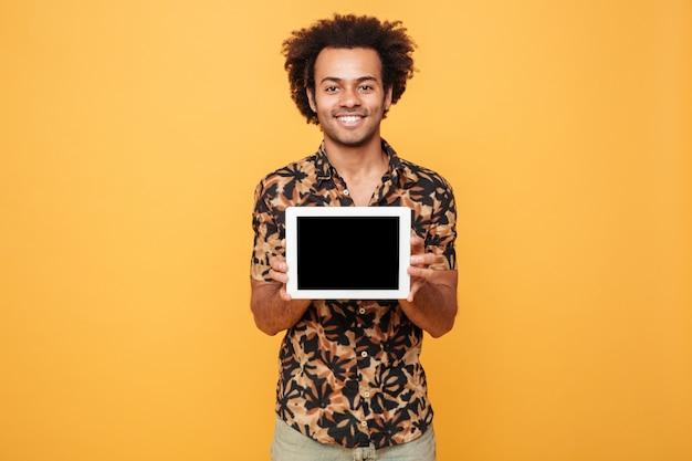 Jovem afro-americano feliz mostrando a tela em branco pc tablet