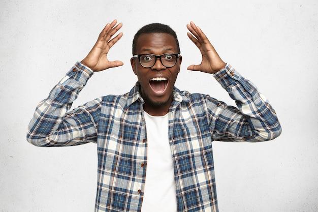 Jovem afro-americano hippie espantado com óculos da moda e camisa xadrez