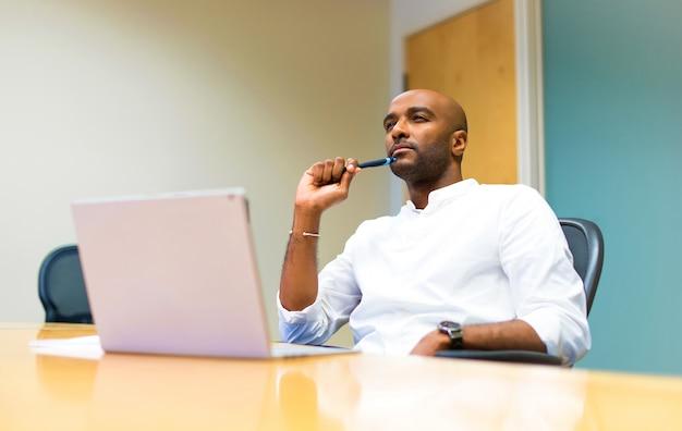 Jovem, afro americano, homem negócios, em, escritório, com, seu, laptop, pensando