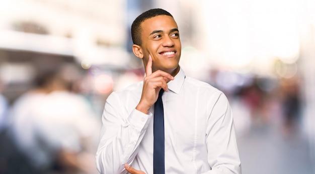 Jovem, afro americano, homem negócios, pensando, um, idéia, enquanto, olhar, cima, cidade