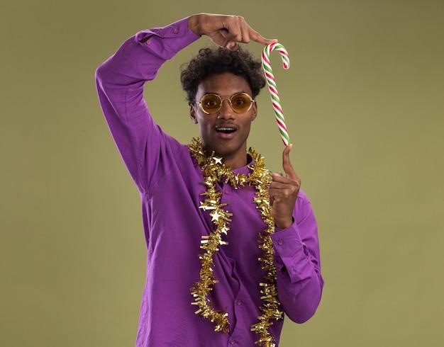 Jovem afro-americano impressionado usando óculos com guirlanda de ouropel em volta do pescoço segurando o bastão de doces de natal verticalmente olhando para a câmera isolada em um fundo verde oliva com espaço de cópia