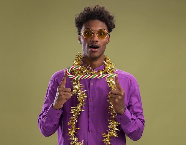 Jovem afro-americano impressionado usando óculos com guirlanda de ouropel no pescoço, segurando o bastão de doces de natal horizontalmente, olhando para a câmera isolada sobre fundo verde oliva