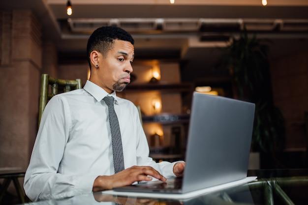 Jovem afro-americano indignado, laptop, em uma camisa branca, dentro de casa