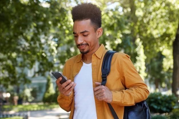Jovem afro-americano insatisfeito de camisa amarela, conversando ao telefone com seus amigos e caminhando no parque, olha para o gadget com expressão ressentida, seu amigo atrasado.