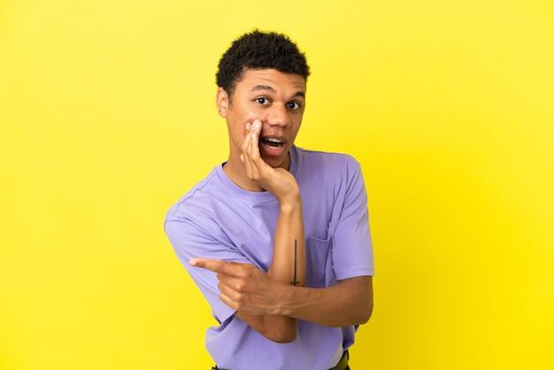 Jovem afro-americano isolado em um fundo amarelo apontando para o lado para apresentar um produto e sussurrando algo