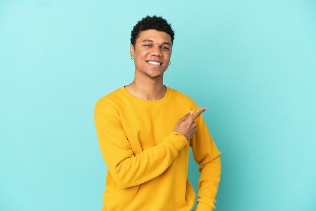 Jovem afro-americano isolado em um fundo azul apontando para o lado para apresentar um produto