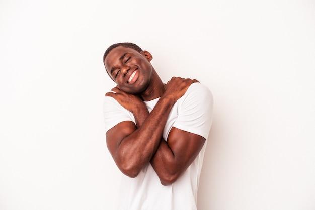 Jovem afro-americano isolado em um fundo branco abraços, sorrindo despreocupado e feliz.
