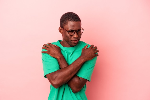 Jovem afro-americano isolado em um fundo rosa abraços, sorrindo despreocupado e feliz.