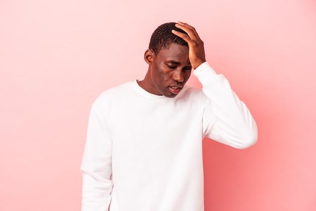 Jovem afro-americano isolado em um fundo rosa cansado e com muito sono, mantendo a mão na cabeça.