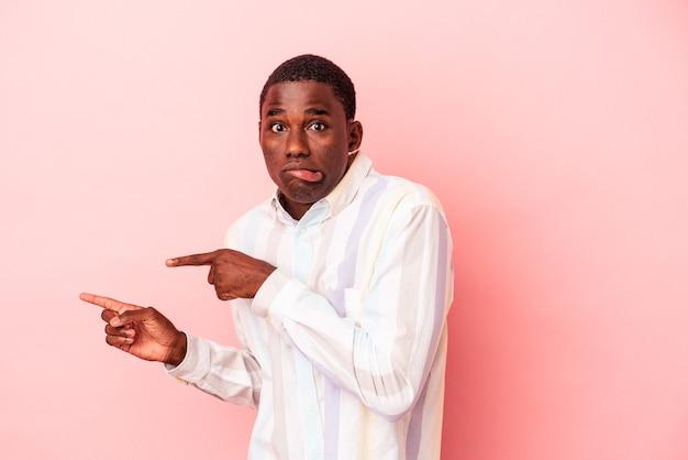 Jovem afro-americano isolado em um fundo rosa chocado, apontando com o dedo indicador para um espaço de cópia.
