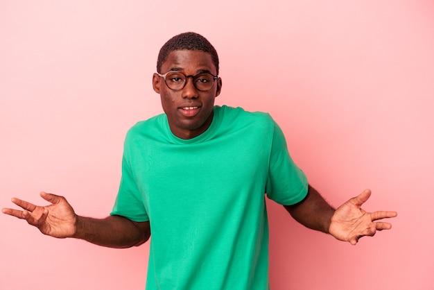 Jovem afro-americano isolado em um fundo rosa duvidando e encolhendo os ombros em gesto de questionamento.