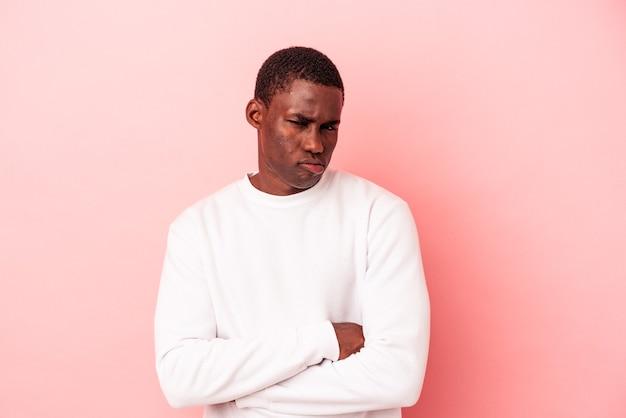 Jovem afro-americano isolado em um fundo rosa infeliz olhando na câmera com expressão sarcástica.