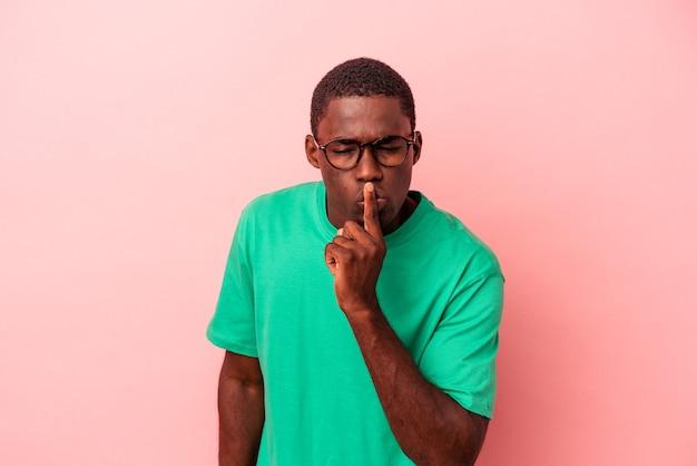 Jovem afro-americano isolado em um fundo rosa, mantendo um segredo ou pedindo silêncio.