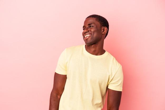Jovem afro-americano isolado em um fundo rosa relaxado e feliz rindo, pescoço esticado, mostrando os dentes.