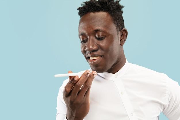 Jovem afro-americano isolado na expressão facial de fundo azul do estúdio