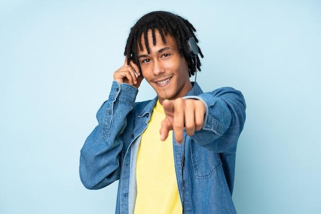 Jovem afro-americano isolado na parede azul, ouvindo música e apontando para a frente