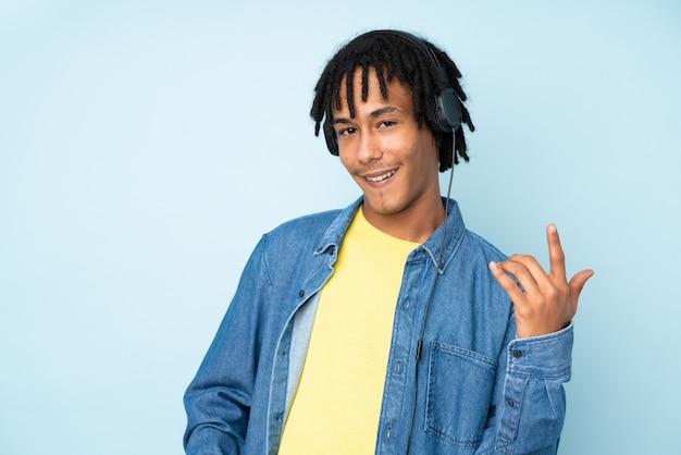 Jovem afro-americano isolado na parede azul, ouvindo música e fazendo gesto de guitarra
