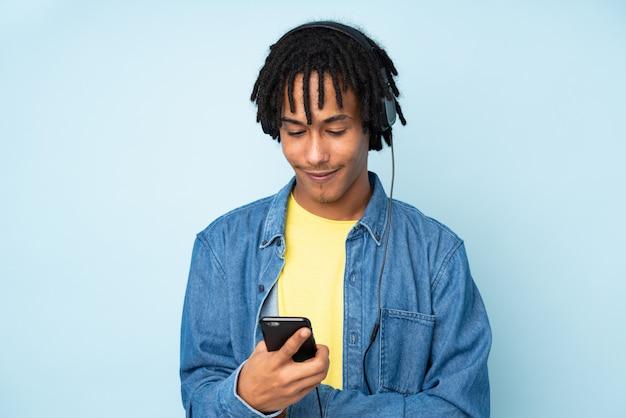 Jovem afro-americano isolado na parede azul, ouvindo música e olhando para o celular