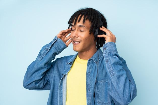 Jovem afro-americano isolado na parede azul, ouvir música e cantar