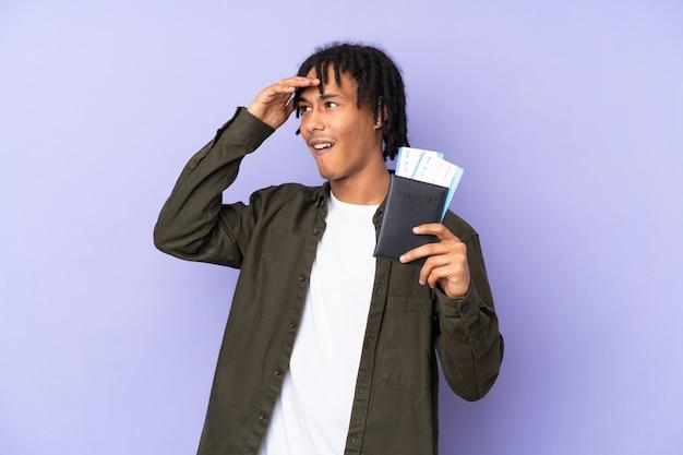 Jovem afro-americano isolado na parede roxa em férias com bilhetes de passaporte e avião enquanto procura algo à distância