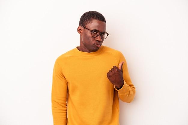 Jovem afro-americano isolado no fundo branco chocado apontando com o dedo indicador para um espaço de cópia.