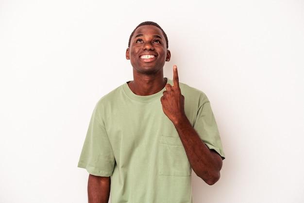 Jovem afro-americano isolado no fundo branco indica com os dois dedos anteriores mostrando um espaço em branco.