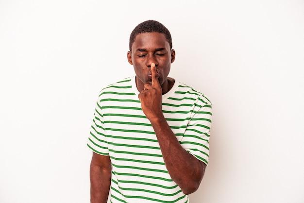 Jovem afro-americano isolado no fundo branco, mantendo um segredo ou pedindo silêncio.