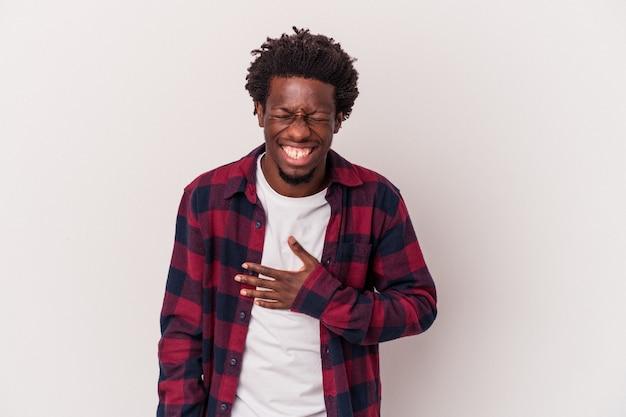 Jovem afro-americano isolado no fundo branco ri alto, mantendo a mão no peito.