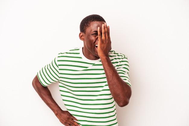 Jovem afro-americano isolado no fundo branco, se divertindo, cobrindo metade do rosto com a palma da mão.