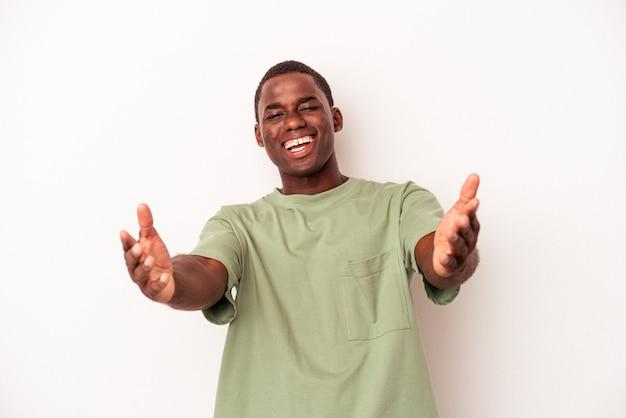 Jovem afro-americano isolado no fundo branco se sente confiante em dar um abraço para a câmera.