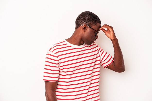Jovem afro-americano isolado no fundo branco, tendo uma dor de cabeça, tocando a frente do rosto.