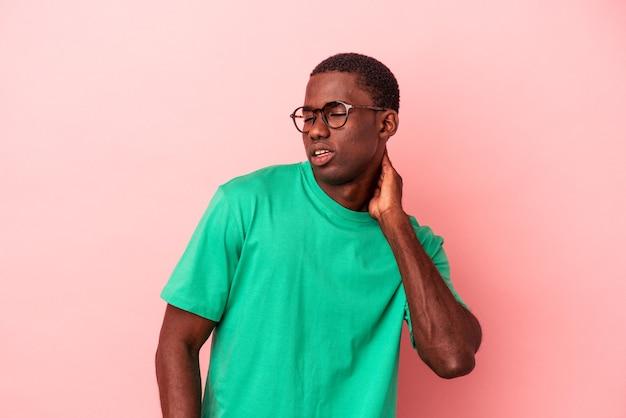 Jovem afro-americano isolado no fundo rosa, sofrendo de dor no pescoço devido ao estilo de vida sedentário.