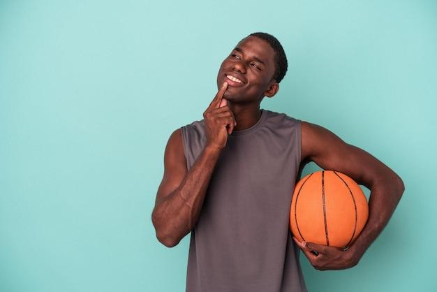 Jovem afro-americano jogando basquete isolado em um fundo azul, olhando de soslaio com expressão duvidosa e cética.
