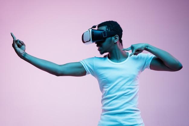 Jovem afro-americano jogando em óculos vr em luz de néon em fundo gradiente. retrato masculino