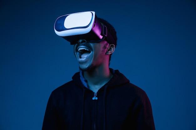 Jovem afro-americano jogando em óculos vr na luz de néon no gradiente.