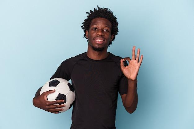 Jovem afro-americano jogando futebol isolado em um fundo azul alegre e confiante, mostrando um gesto de ok.