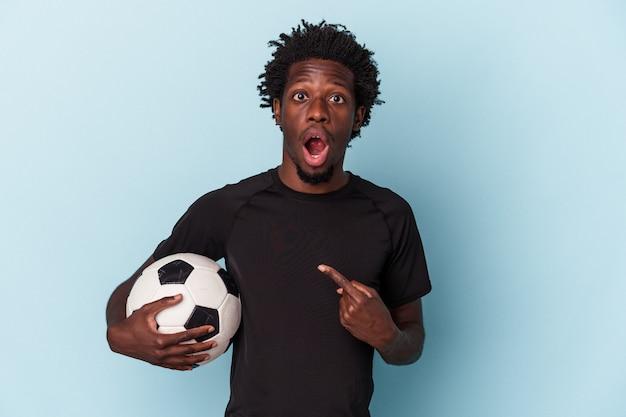 Jovem afro-americano jogando futebol isolado em um fundo azul apontando para o lado