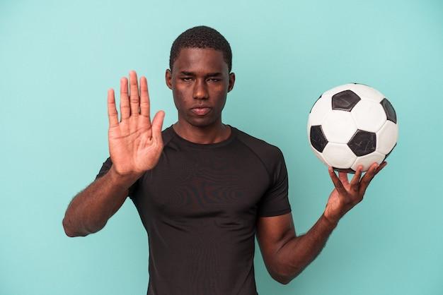Jovem afro-americano jogando futebol isolado em um fundo azul em pé com a mão estendida, mostrando o sinal de pare, impedindo-o.