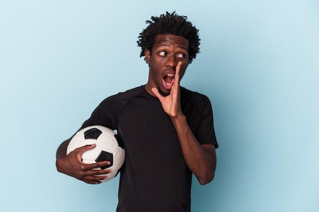 Jovem afro-americano jogando futebol isolado em um fundo azul está contando uma notícia secreta de travagem e olhando para o lado