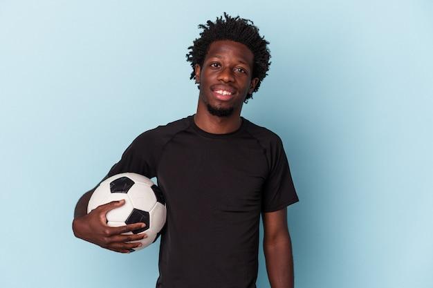Jovem afro-americano jogando futebol isolado em um fundo azul feliz, sorridente e alegre.