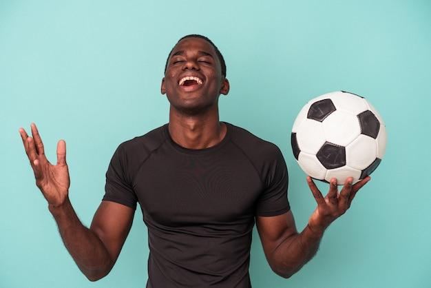 Jovem afro-americano jogando futebol isolado em um fundo azul, recebendo uma agradável surpresa, animado e levantando as mãos.