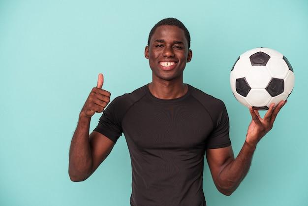 Jovem afro-americano jogando futebol isolado em um fundo azul, sorrindo e levantando o polegar