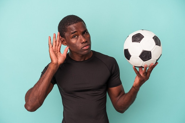 Jovem afro-americano jogando futebol isolado em um fundo azul, tentando ouvir uma fofoca.