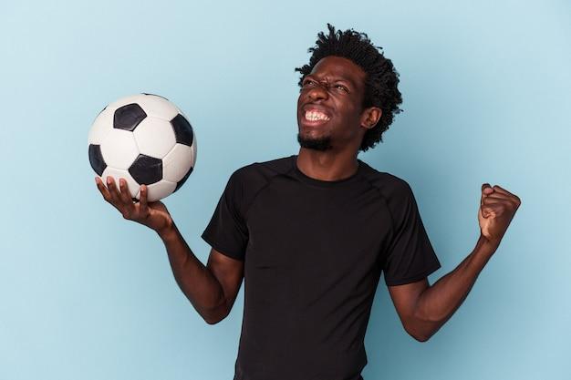 Jovem afro-americano jogando futebol isolado em um fundo azul.
